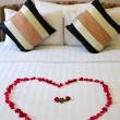 Heart of rose petals laid out on the bed — Stock Photo