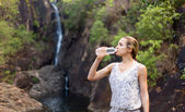 Young healthy woman drinks water from bottle.Outdoor — Stock Photo