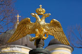 Golden double-headed eagle on a background of blue sky — Stock Photo