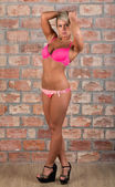 Sexy girl in pink lingerie against a brick wall — Stock Photo