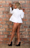 Sexy girl in a white jacket and buttocks with a brick wall — Stock Photo