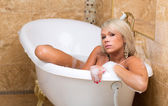 Beautiful tanned girl is taking a luxurious bath. — Stock Photo