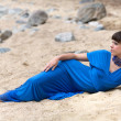 Girl in a dress lying on the sand — Stock Photo