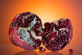 Ripe red pomegranate, break in half, juicy corn — Stock Photo