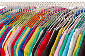 Colored shirts on hangers steel closeup. — Stock Photo