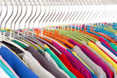 Collection of colored shirts on steel hangers — Stock Photo