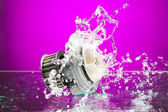 Auto parts, engine cooling pump in spurts of water on purple bac — Stock Photo