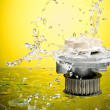 Auto parts, engine cooling pump in water splash on yellow gradie — Stock Photo #50582555