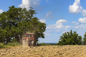 Tractor plowing the land — Stock Photo