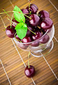 Sweet cherry fruits in glass goblet with mint leaf — Stock Photo