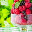Sweet fresh fruits in glass goblet with mint leaf - Stockfoto
