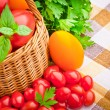 Wicker basket full of fresh tomatoes and cherry tomatoes — Stock Photo