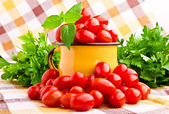 Yellow mug full of fresh cherry tomatoes — Stok fotoğraf