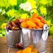 Delicious dried apricots and dates in tin pail — Stock Photo