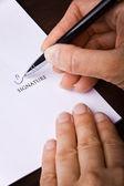 Main de l'homme avec un stylo, signature d'un document — Photo