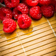 Delicious fresh raspberries on a wooden background — Stock Photo