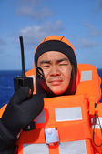 Seaman in immersion suit and with portable radio — Stock Photo