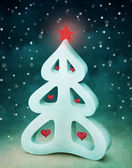 Festive winter background with white spruce and red hearts and star — Stock Photo