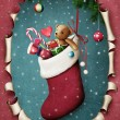 Hanging christmas sock with presents in oval frame — Стоковая фотография