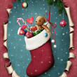 Hanging christmas sock with presents in oval frame — Stock Photo