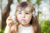 Little girl blowing soap bubles — Stockfoto