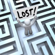 Lost Man Holding Sign in Labyrinth Maze - Stock Photo