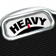 Stock Photo: Heavy Word on Scale Measuring Weight or Mass