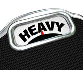 Heavy Word on Scale Measuring Weight or Mass — Stock Photo