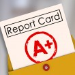 Report Card with A or Plus stamped on it within a yellow envelope — Stock Photo #48128801