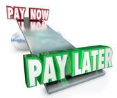 Pay Now Vs Later words on a see saw or balance — Stok fotoğraf