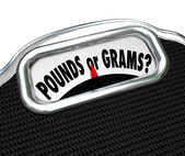 Pounds or Grams words on a display of a scale — Stock Photo