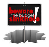 Beware the Budget Sinkhole words on a sign in a hole — Stock Photo