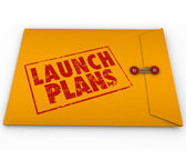 Launch Plans words stamped in red ink on yellow envelope — Stock Photo