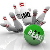 Real bowling ball striking pins marked Fake — Stock Photo