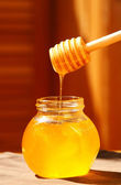 Jar of honey with wood stick — Stock Photo