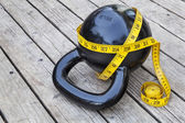 Kettlebell and measuring tape — Stock Photo