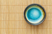 Empty bowl and bamboo mat — Stock Photo