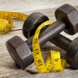 Stock Photo: Iron dumbbells and measuring tape