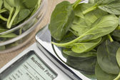 Fresh spinach on diet scale — Stock Photo