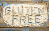Gluten free words in flour — Stock Photo