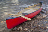 Red canoe with a paddle — Stock Photo