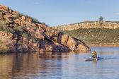 Canoe paddling on a lake — Stock Photo