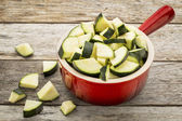 Diced zucchini in stoneware pot — Stock Photo