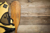 Canoe paddle and life jacket — Stock Photo