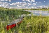 Red canoe on lake shore — Zdjęcie stockowe