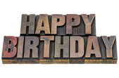 Happy birthday in grunge wood type — Stock Photo