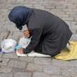 Poor woman on the street begging for money - Stock Photo