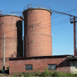 Two brick silos against the blue sky — Stock Photo #18456685