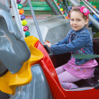 Girl on the merry-go-round in the park - Stock Photo