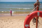 Life buoy on a beach against the sea — Stock Photo